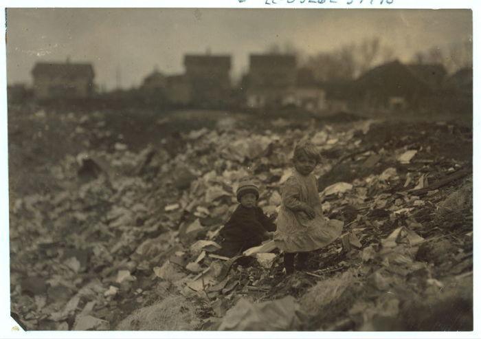 Дети разбирают мусор в поисках пластиковой посуды на свалке в род-Айленде.