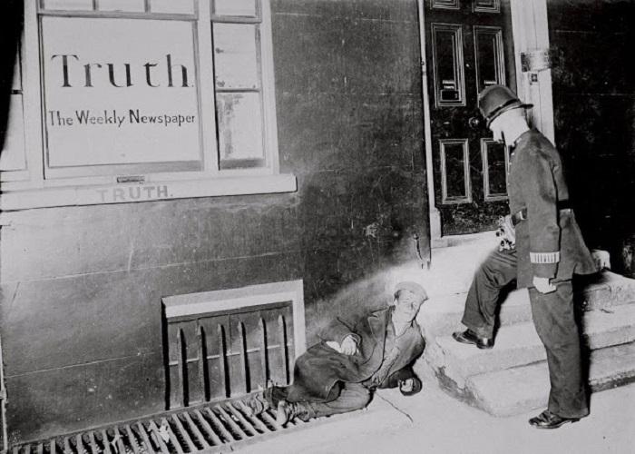 Полицейский проверяет документы у рабочего, который уснул возле редакции лондонской газеты. Великобритания, Лондон, 1902 год.