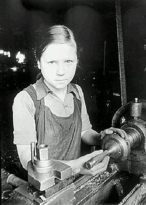 Девочка работает за токарным станком. СССР, Ленинград, 1943 год.