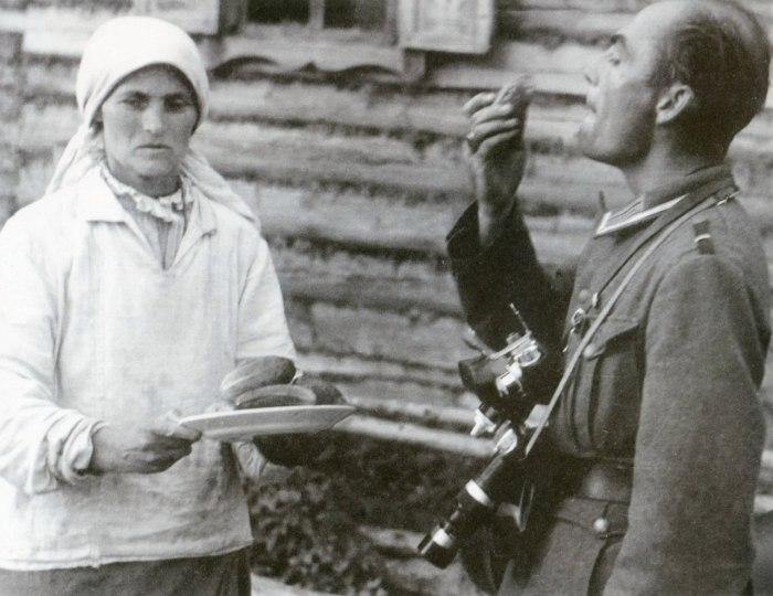 Офицер пробует огурцы в белорусской деревне.