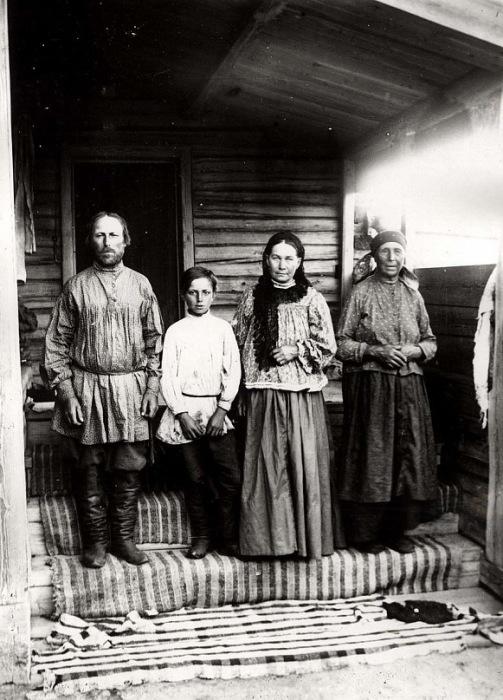 Крестьяне в праздничной одежде стоят на ступеньках крыльца.