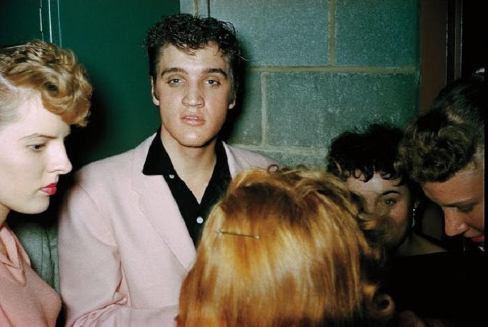 Элвис Пресли раздаёт автографы за кулисами.