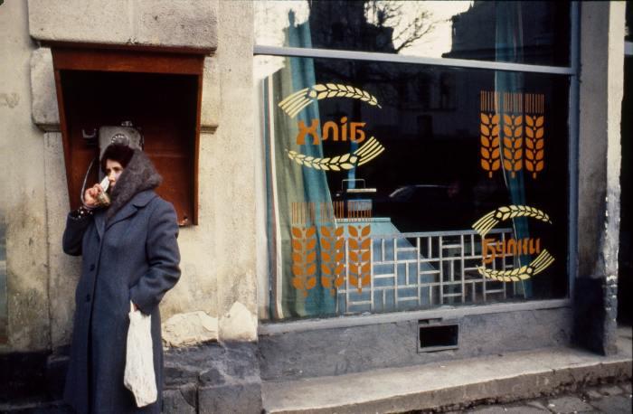 Женщина разговаривает по уличному телефону-автомату.