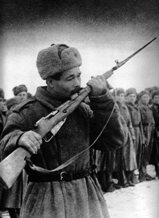 Символичная фотография - солдат целует своё оружие перед боем.