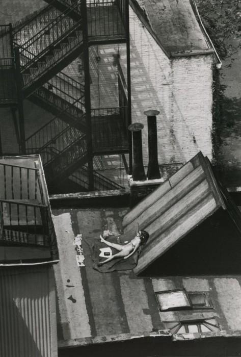 Девушка загорает на крыше дома в солнечный день. США, Нью-Йорк, 1978 год.
