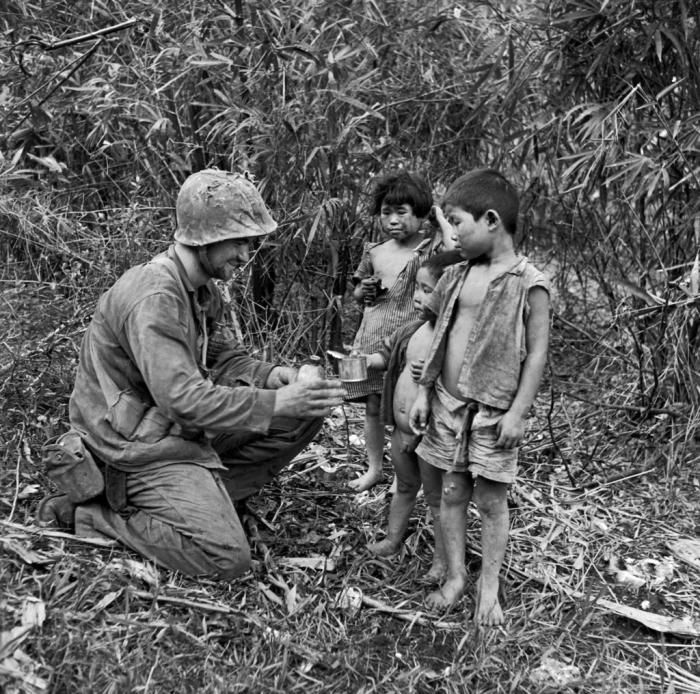 Американский солдат делится водой и едой с тремя детьми. Сайпан, 1944 года.