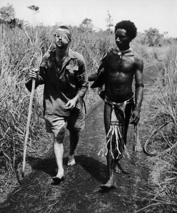 Уроженец Папуа-Новой Гвинеи, сопровождает раненого австралийского солдата, 1942 год.