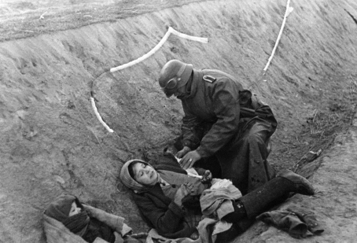 Немецкий солдат наносит повязку раненной русской женщине.