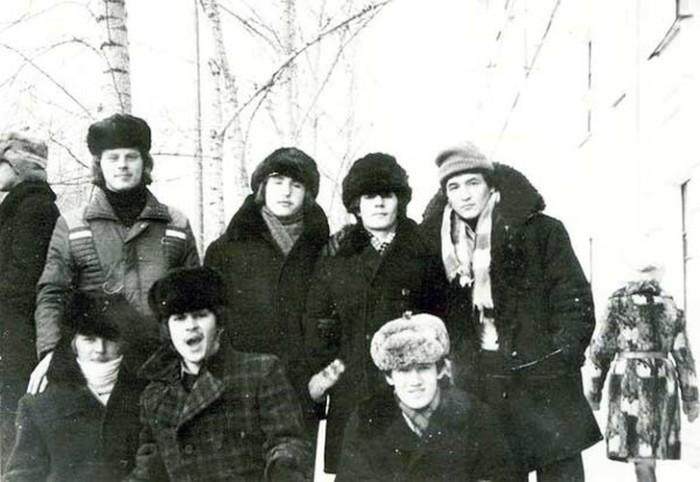 Юноши в зимних куртках с воротниками из искусственного меха и шапками-ушанками.
