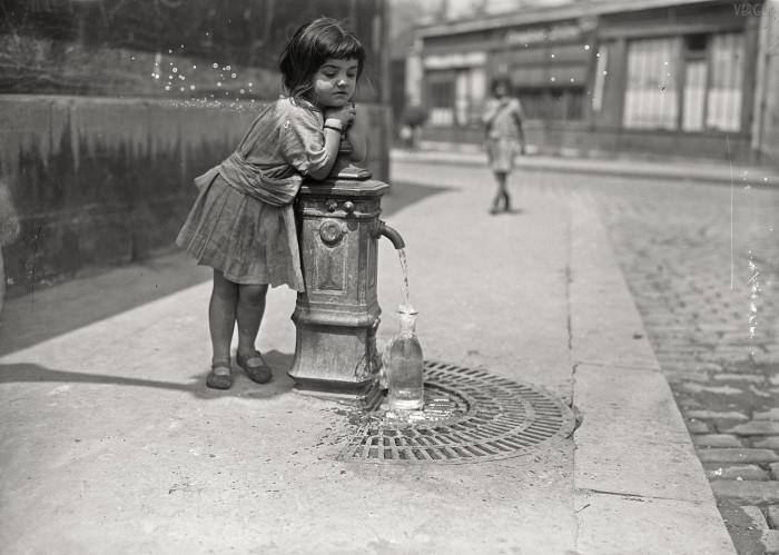 Девочка набирает воду из уличного крана. Франция, Париж, 1921 год.