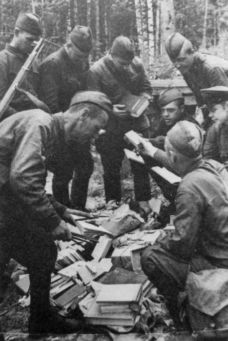 Бойцы покупают книги и бумагу в походной палатке военторга. Ленинградский фронт, 1942 год.