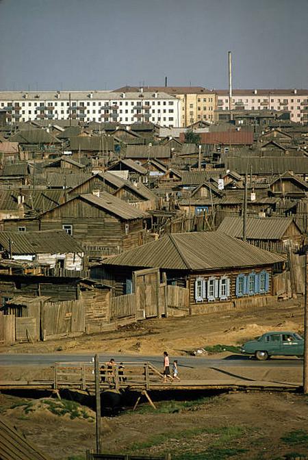 Новые многоквартирные дома возвышаются над старыми избами в Якутске.