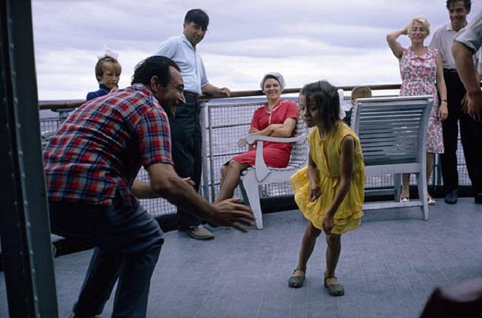 На палубе теплохода один из гидов учит девочку танцевать твист.