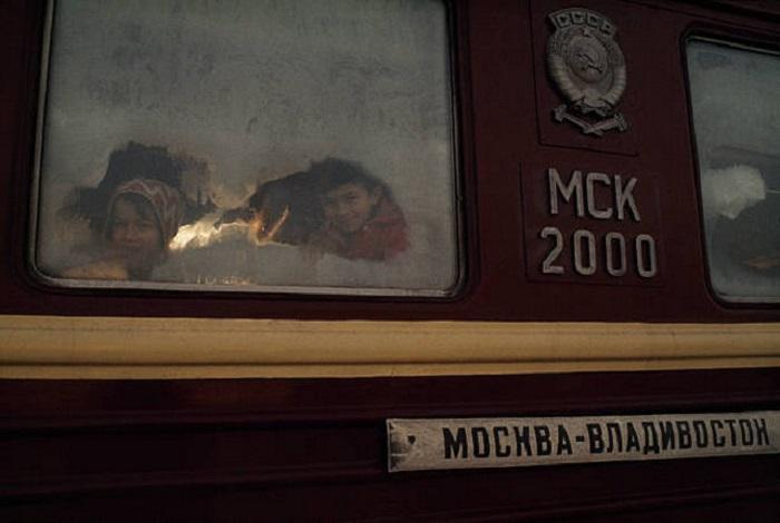 Дети выглядывают из вагона на станции Транссибирской магистрали.