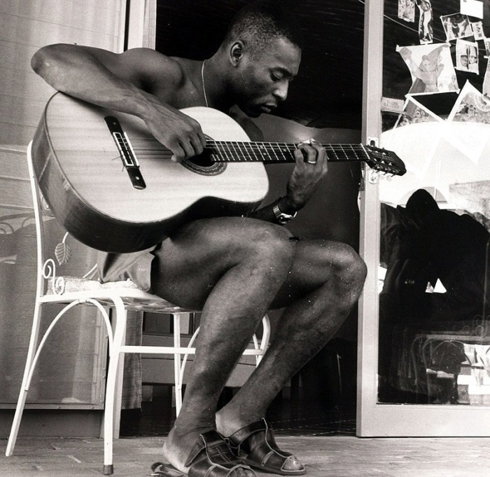 Бразильский футболист играет на гитаре.