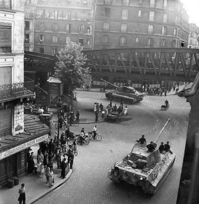 Танки 503-го тяжелого танкового батальона вермахта движутся по улице Парижа в направлении Нормандии. Франция, Июнь 1944 год. Батальон Schwere Panzer-Abteilung 503 — немецкое бронетанковое подразделение, имевшее на вооружении тяжёлые танки Tiger I и Tiger II. Батальон сформирован 6 апреля 1942 года, 21 декабря 1944 года преобразован в тяжёлый танковый батальон «Feldhernhalle» в составе корпуса того же названия.