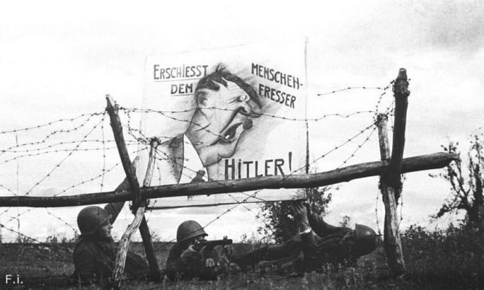 Бойцы рабоче-крестьянской Красной армии вывешивают карикатуру на Гитлера на передовой. Северо-Западный фронт, 1942 год.