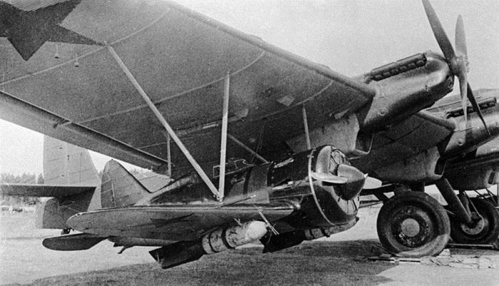 Под крылом самолета ТБ-3 подвешен истребитель И-16 с фугасными бомбами весом 250 кг каждая. Лето 1941 года.