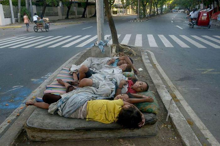 Бездомные дети спят на выброшенном матрасе посреди дороги.