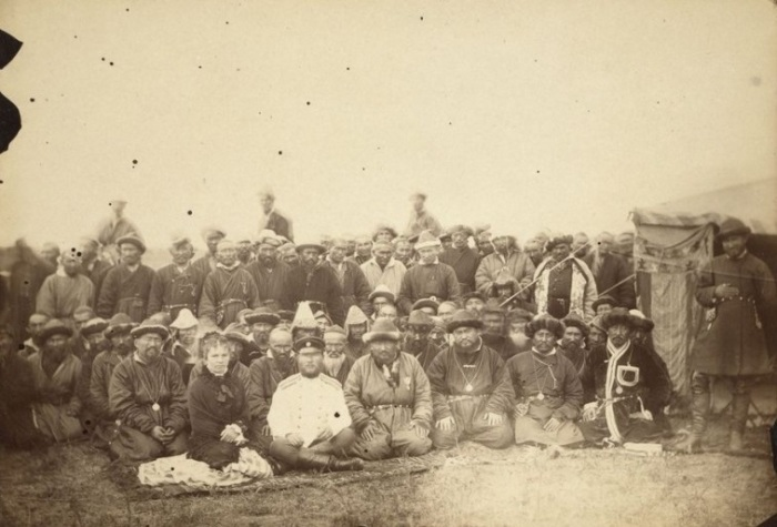 Группа киргизов позирует с начальником каторги перед юртой.