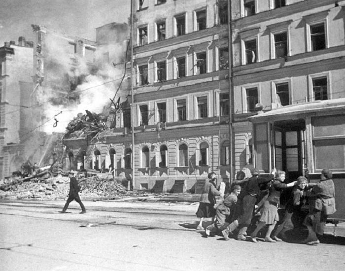 Местные жители передвигают трамвайный вагон от разрушенного здания, 1942 год.