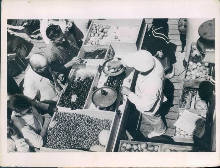 Крестьяне торгуют овощами и фруктами на рынке в 1936 году.