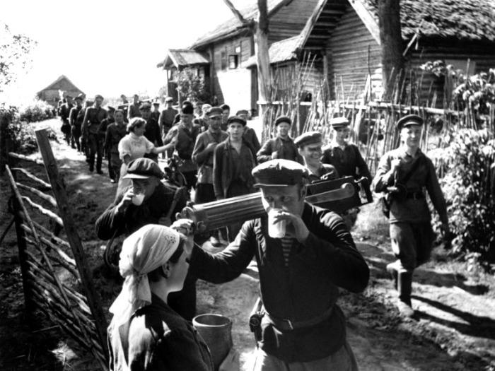 Местные жители встречают партизан, освободивших деревню.