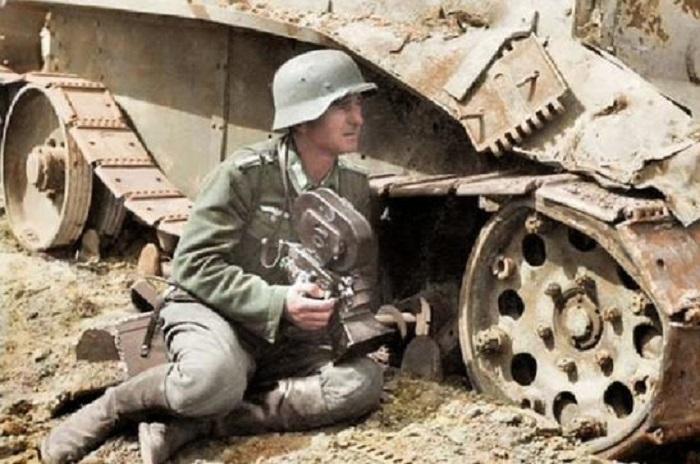 Немецкий военный корреспондент под прикрытием подбитого советского танка БТ-5.