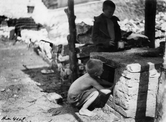 Двое беспризорников у печи. СССР, Москва, Шаболовский детский дом, 1925 год.