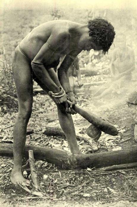 Молодой человек рубит ствол каменным топором.