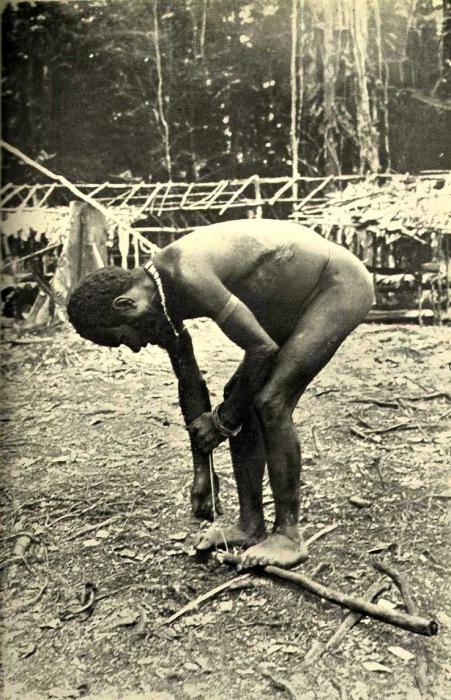 Мужчина добывает огонь трением бечевки по дереву.