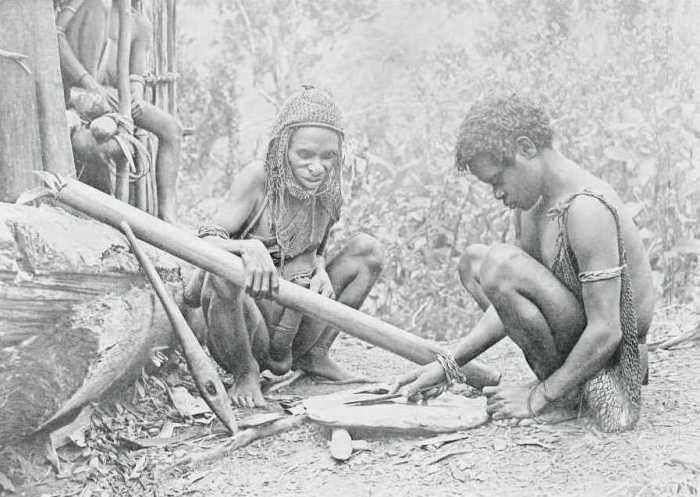 Туземцы точат каменный нож.