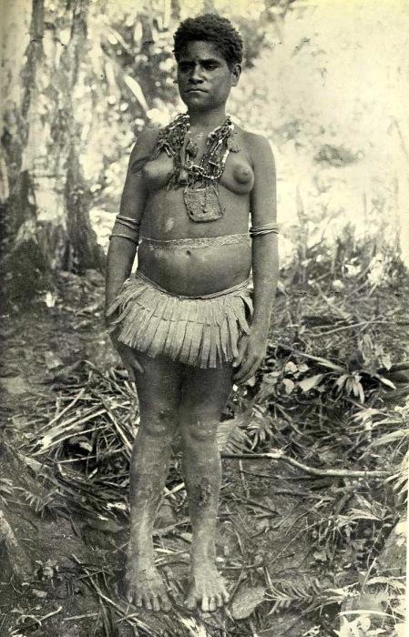 На женщине одеты ожерелья и амулеты. Юбка сделана из полосок листьев пандануса.