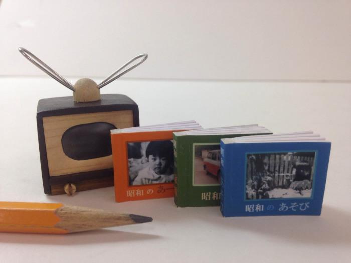 Три японские книги с чехлом в форме телевизора, через экран которого видна картинка с обложки.