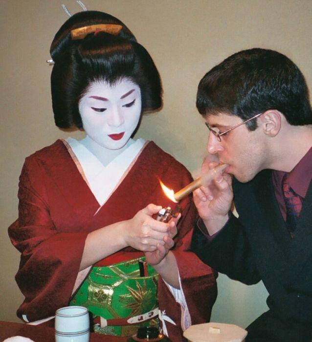 Гейша подкуривает сигару иностранному гостю. | Фото: en.wikipedia.org.