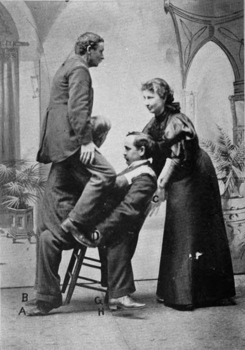 Лулу Херст поднимает трех мужчин на стуле.   Фото: en.wikipedia.org.