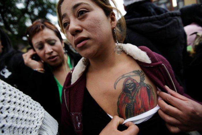 Мексиканка демонстрирует татуировку Санта Муэрте. | Фото: thedailybeast.com.