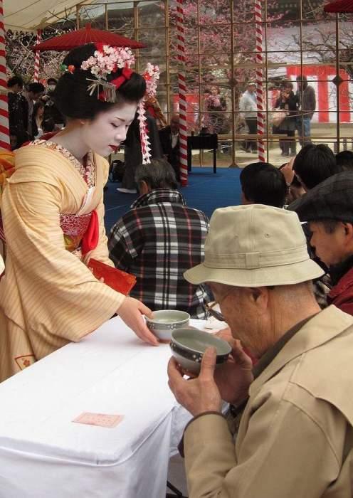 Майко раздает чай на фестивале цветения сливы в храме Китано-тэммангу. | Фото: en.wikipedia.org.