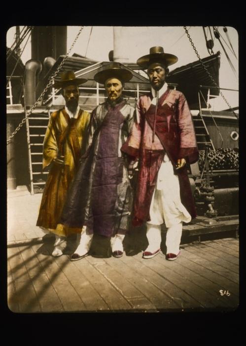 Три корейских джентльмена стоят на палубе судна.