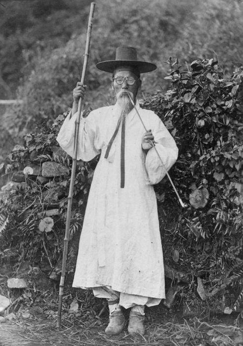 Кореец в традиционном халате ханбок и сапогах. Он носит конский хвост и бамбуковую шляпу.
