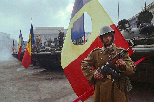 Румынский солдат на фоне флага с вырезанным гербом. | Фото: gazeta.ru.