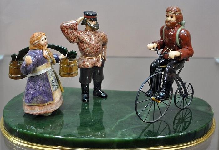 «Легенда об Артамонове»<br>Существует легенда, что первый велосипед был изготовлен в 1800 году крепостным тагильским мастеровым Артамоновым Ефимом Михеевичем. Материал: агат-переливт, чароит, кахолонг, яшма, мрамор, родонит, нефрит, гранит, морион, обсидиан, сард, кровавик, аванюрин, окаменелое дерево, горный хрусталь, тигровый глаз металл. 2001 г. Автор: Виктор Васильев.