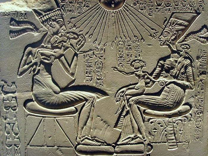 Эхнатон целует старшую дочь Меритатон, её сестра Макетатон сидит на коленях Нефертити, а младшая Анхесенпаатон играет с серьгами матери.