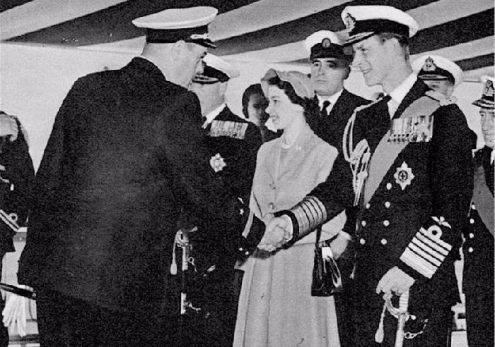 Елизавета II и её муж Филипп, приветствуют морского офицера Рудакова.