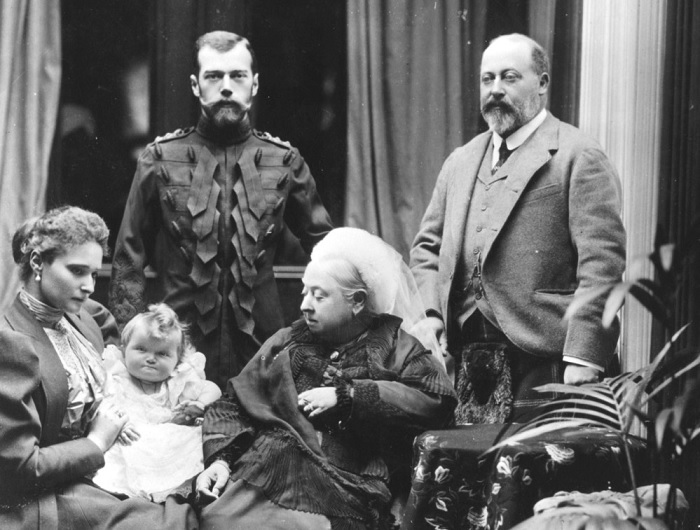 Королева Виктория в старости. Справа - ее старший сын Эдуард VII, слева - молодая семья русского царя: Николай II, его жена Александра и их ребенок Ольга Александровна, правнучка Виктории