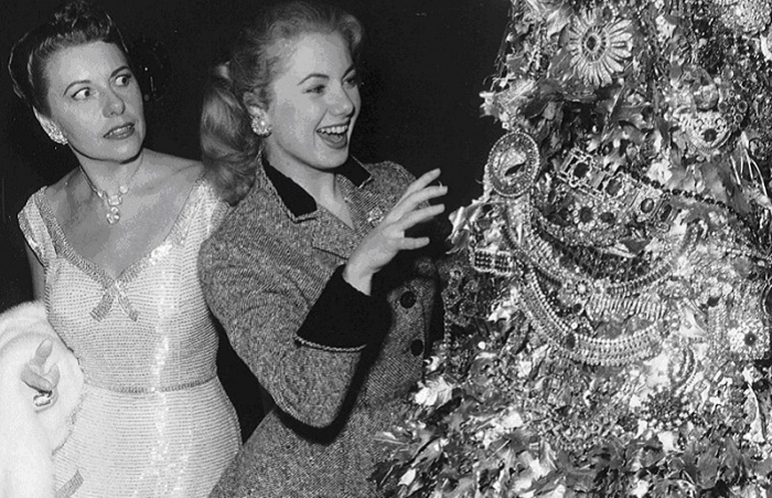 Джоан Касл с ужасом смотрит на Ширли Джонс, которая пытается потрогать ошеломляющую рождественскую елку, сделанную из драгоценностей Джозефа