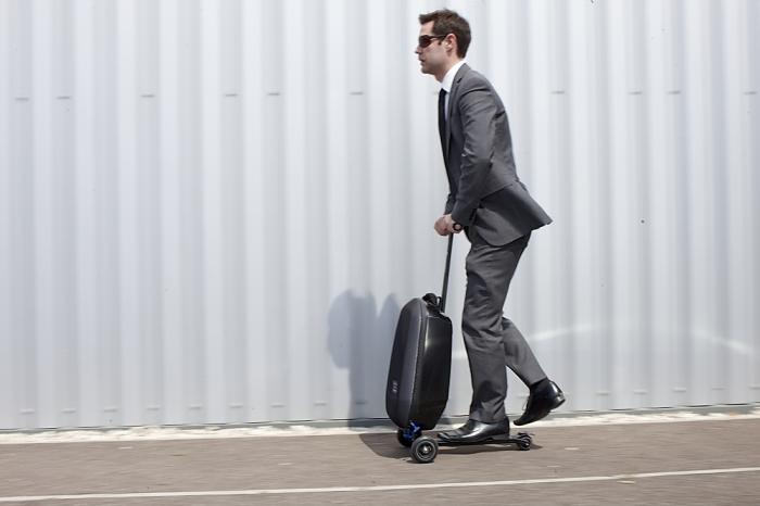 Человек с пустым чемоданом катается на самокате./Фото: www.dragtimes.ru