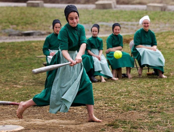Девочка-подросток из семьи амишей играет в бейсбол.