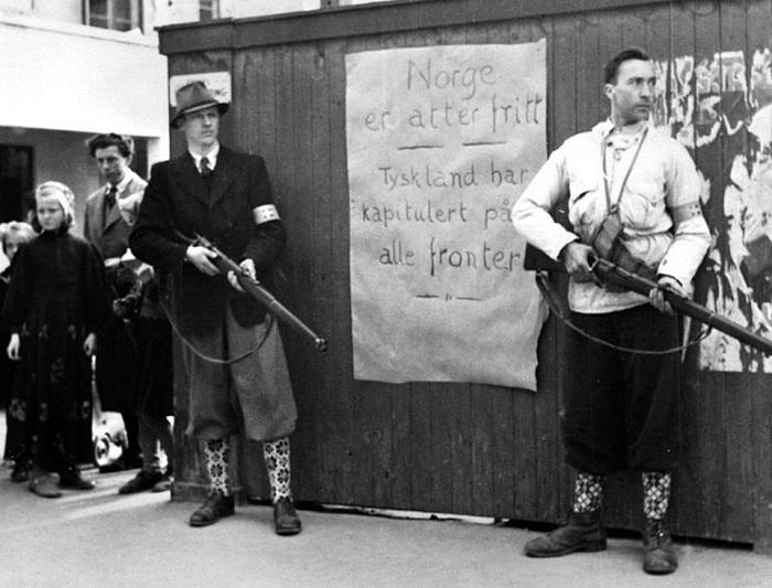 Участники норвежского сопротивления на фоне плаката «Норвегия снова свободна», город Берген.