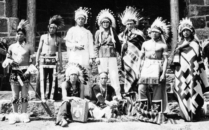 Мужчины народа крик в национальных костюмах.